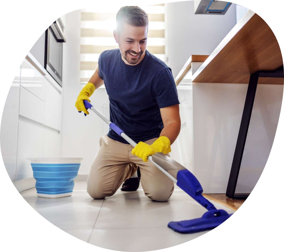 agent accroupi qui nettoie le sol sous un meuble