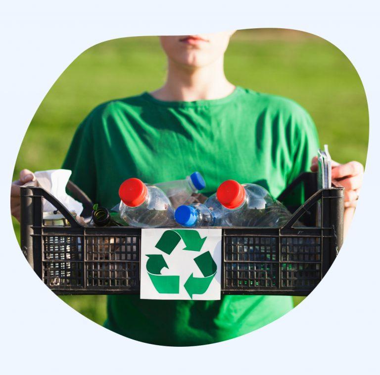 femme qui tient un bac rempli de bouteilles recyclables