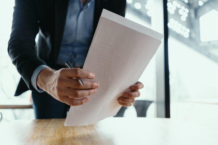 homme qui tient des papiers administratifs dans ses mains